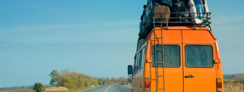 The small bus with bags on a roof